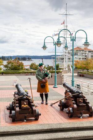 highlander: Nanaimo, Canad� - 9 de julio: Un jugador de la gaita escocesa lleva a cabo antes de la ceremonia de tiro de ca��n a diario en el basti�n hist�rico de 9 de julio de 2016. La ceremonia diaria ha sido una atracci�n durante las �ltimas tres d�cadas. tradici�n escocesa de Nanaimo surgi� de la