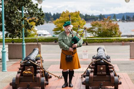 decades: NANAIMO, CANADA - JULY 9: A Scottish bagpipe player performs prior to the daily cannon firing ceremony at the historic Bastion July 9, 2016. The daily ceremony has been an attraction over the last three decades. Nanaimos Scottish tradition arose from the