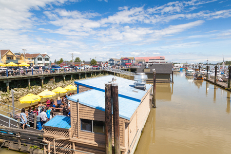 frontier: RICHMOND, CANADA - JULY 10: Diners at the seaside village of Steveston Fishermans Wharf eating at one of the floating restaurants July 10, 2016. A 19th-century frontier seaport more than 100 years ago, the place has become a picturesque commercial fishin Editorial