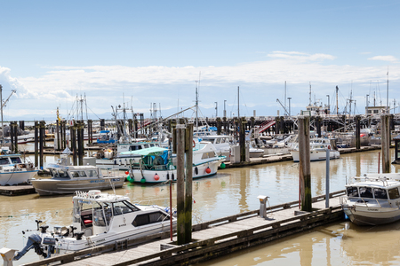 frontier: RICHMOND, CANADA - JULY 10: Colorful boats and trawlers dock at the seaside village of Steveston Fishermans Wharf in Richmond near Vancouver July 10, 2016. A 19th-century frontier seaport more than 100 years ago, the place has become a picturesque commer