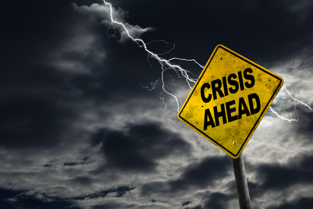 predict: Crisis Ahead sign against a stormy background with lightning and copy space. Dirty and angled sign adds to the drama. Concept of political, financial, social, health crisis.