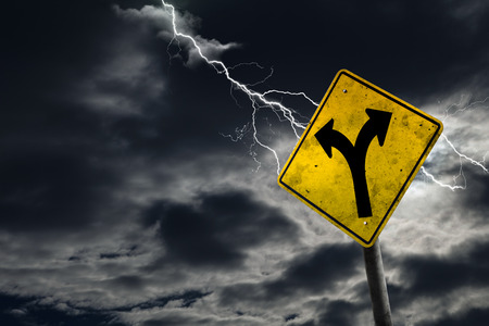 Folk in road sign against a stormy background with lightning and copy space. Dirty and angled sign adds to the drama.