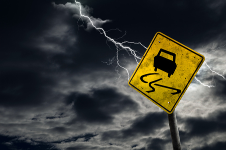 adds: Slippery when wet road sign against a stormy background with lightning and copy space. Dirty and angled sign adds to the drama. Stock Photo