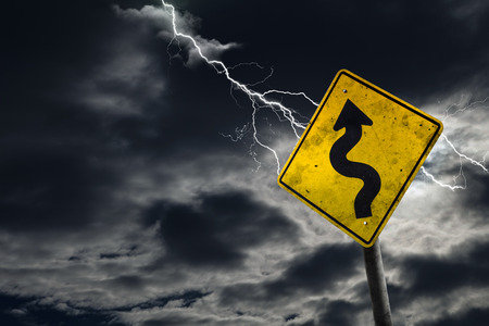 adds: Winding road sign against a stormy background with lightning and copy space. Dirty and angled sign adds to the drama. Stock Photo