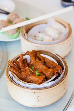 Gestoofde kip voeten dim sum in bamboe steamer is een populair gerecht in het Kantonees restaurants in Hong Kong. Stockfoto