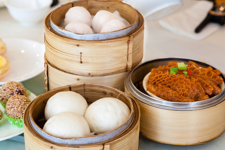 Steamed Chinese dim sum served in bamboo steamers, including buns, braised beef tripes and shrimp dumplings. Dim sum is a unique culinary art form that originated with the Cantonese in southern China and Hong Kong. Stock Photo