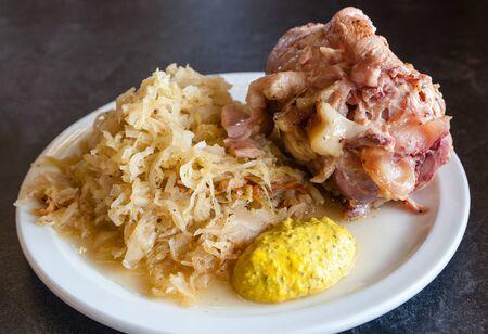Traditional German ham hock or pork knuckle served with sauerkraut. Stock Photo