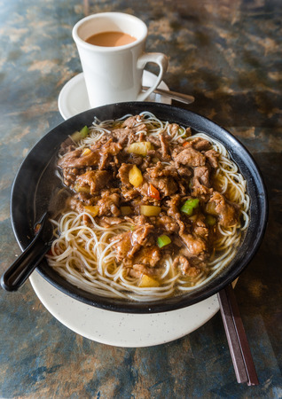 favorite soup: Satay beef soup noodles is featured in many Hong Kong cafes. Typically served with milk tea, the local dish is a favorite breakfast or lunch item for Hong Kongers. Vertical orientation.