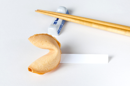 Fortune cookie with blank slip and Chinese chopsticks in background. Stock Photo