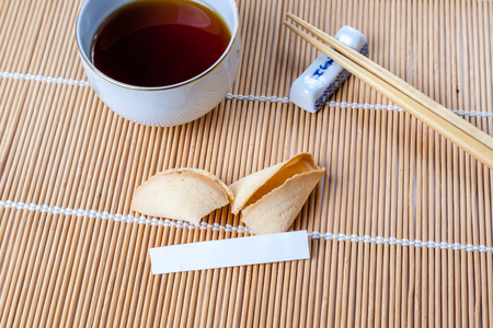 Broken fortune cookie with blank slip on bamboo mat with Chinese chopsticks and tea in Chinese cup.