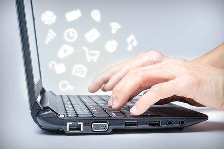 Handen die op toetsenbord met gemeenschappelijke media pictogrammen typen die van laptop toenemen. Multi-tasking op internet.