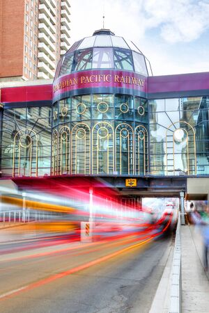 Calgary, Canada - June 14, 2016: Traffic tail lights streak along downtown Calgary on 9th Avenue under the Canadian Pacific (CP) Railway glass tower cupola. Canadian Pacific Rail has played an important role in Calgarys economy for more than 100 years. F