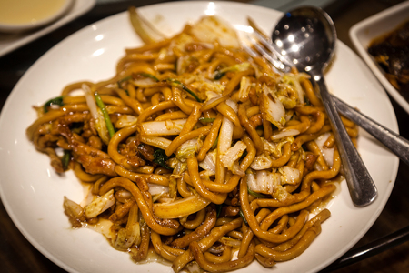 nappa: Shanghai fried noodles chow mein is a popular Chinese dish stir-fried with pork, napa cabbage and onion. The dish is a staple of Shanghai cuisine and served at dumpling houses. Stock Photo
