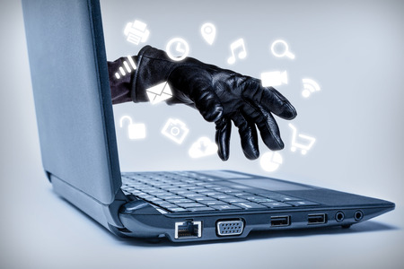 A gloved hand reaching out through a laptop with common media icons flowing, signifying a cybercrime or Internet theft while using various Internet media. Banque d'images
