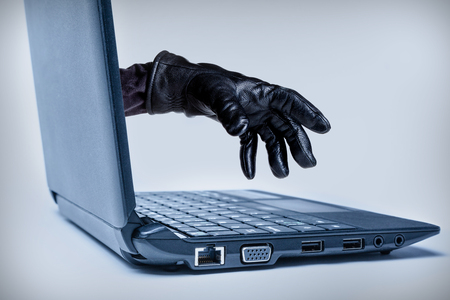 A gloved hand reaching out through a laptop, signifying a cybercrime or Internet theft while using Internet media. Banco de Imagens