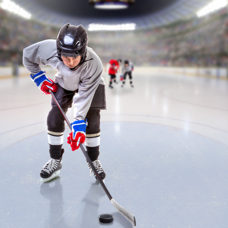 wee: Boy hockey player handling puck on ice with arena full of fans in the stands and copy space. 3D rendering of hockey rink arena.