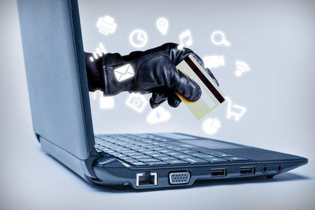 A gloved hand reaching out through a laptop holding debit or credit card with common media icons flowing, signifying a cybercrime or Internet theft while using various Internet media.