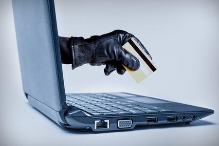 사이버 범죄 또는 인터넷 절도를 나타내는 직불 카드 또는 신용 카드를 들고 노트북을 통해 밖으로 도달하는 낀된 손.
