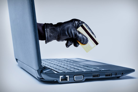 A gloved hand reaching out through a laptop holding debit or credit card, signifying a cybercrime or Internet theft. Stock Photo