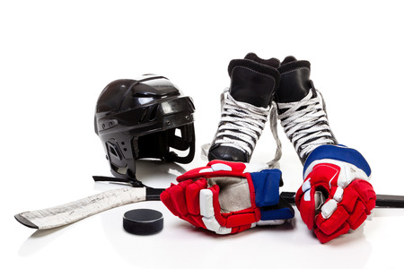 Ice hockey equipment featuring safety helmet, pair of skates, gloves, stick and a hockey puck. Isolated on white background.