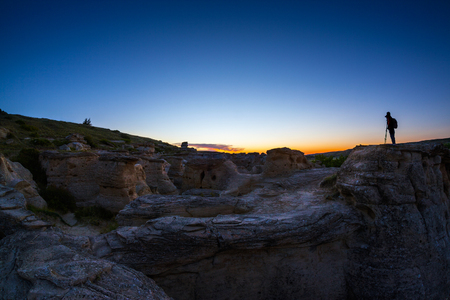 national historic site: Silhouette of photographer on top of the hoodoos at Writing on the Stone Provincial Park in Alberta waiting to catch the golden sunrise at dawn. The area, also known as �ísínaipi National Historic Site, contains the largest concentration of First Nati