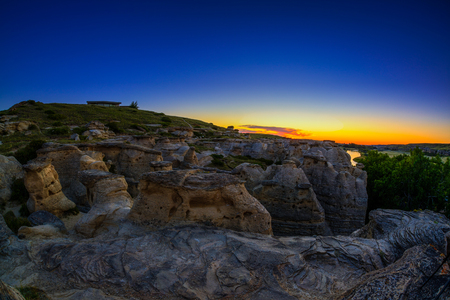 Golden sunrise over the Hoodoo badlands at Writing on Stone Provincial Park and �ísínaipi National Historic Site in Alberta, Canada. The area contains the largest concentration of First Nation petroglyphs (rock carvings) and pictographs (rock painting