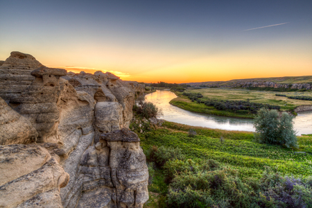Golden sunrise over the Hoodoo badlands at Writing-on-Stone Provincial Park in Alberta, Canada. The area contains the largest concentration of First Nation petroglyphs (rock carvings) and pictographs (rock paintings) on the great plains of North America.