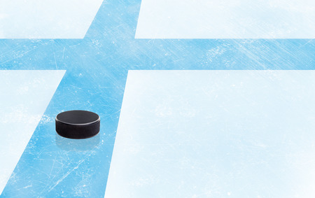 Finland flag embedded on ice hockey rink surface with puck and copy space. Low angle view.
