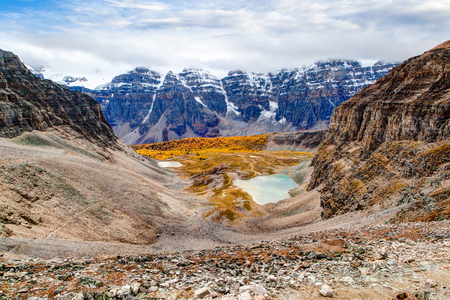 valley below: Hiking view atop Sentinel Pass near Lake Louise in Banff National Park, Alberta, showing golden Larch trees and snow-capped Valley of Ten Peaks in the background with Minestimma Lakes in the valley below.