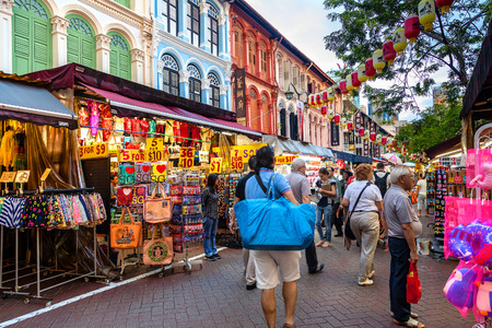 Singapore - December 12, 2014: Shoppers and tourists visit Singapore Chinatown for bargain souvenirs and authentic local food. The old, colorful Victorian-style shophouses are a trademark of this popular area. Editorial