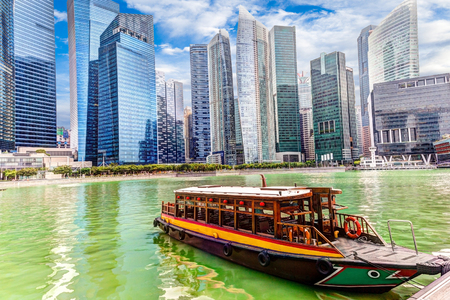 A bumboat docks at Marina Bay with background skyscrapers in the Singapore business district. HDR rendering. Stock Photo