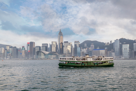 A Ferry crossing Victoria Harbor from Tsim Sha Tsui with downtown Hong Kongs financial district skyline in the background.