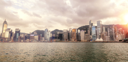 Wide-angle panorama of Hong Kongs Central District skyline on Victoria Harbor at sunset. Viewed from downtown Tsim Sha Tsui on Hong Kong Island. HDR rendering. Stock Photo