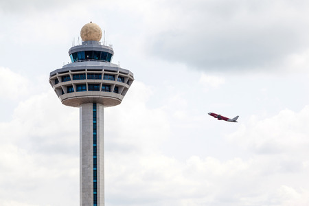 Singapore Changi International Airport traffic controller tower with airplane taking off in the background. The unique airport tower is one of the most recognizable icons of Singapore.
