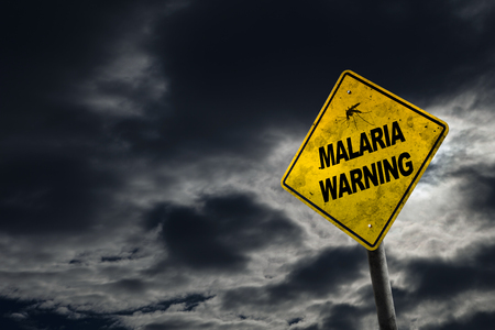 Malaria warning sign against a stormy background with dirty and angled sign for drama. Malaria is a life-threatening disease caused by parasites that are transmitted to people through the bites of infected female Anopheles mosquitoes Фото со стока
