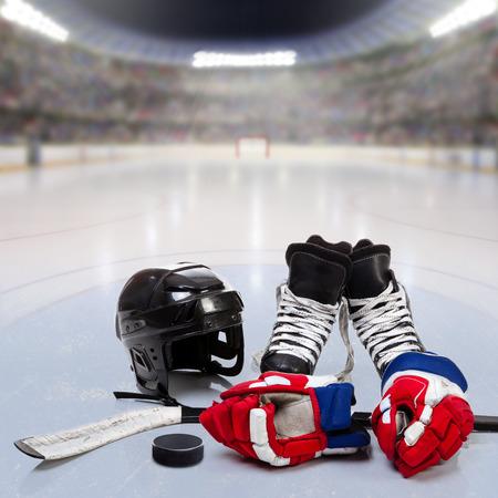 Hockey helm, handschoenen, schaatsen, stick en puck op ijs in fictieve arena met fans op de tribunes en kopie ruimte. 3D-weergave van hockey arena.