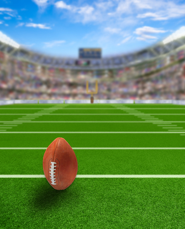 foreground focus: American football stadium full of fans in the stands with ball ready for kickoff or field goal on the field. Deliberate focus on foreground and copy space.