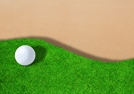 Golf ball on edge of sand trap bunker with copy space.