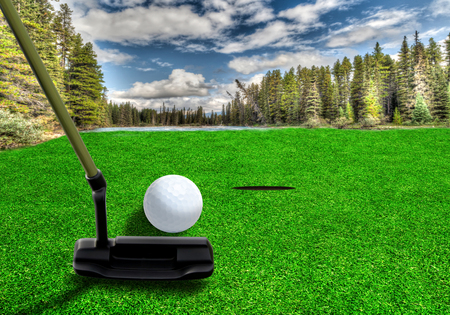 퍼 터 클럽을 사용 하여 이른 아침에 호수와 산의 경치와 함께 아름 다운 골프 코스에서 골프 공을 칠 골퍼. 고의적 인 렌즈 플레어. 스톡 콘텐츠
