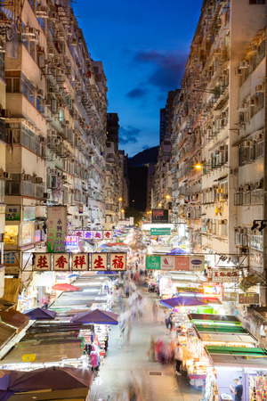 Night market in busy Fa Yuen Street in Mong Kok, Hong Kong, China. The area is popular with tourists and locals for its cheap food and fashion clothing. Long exposure for crowd motion effect. Vertical orientation.