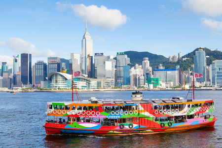 HONG KONG - JULY 10, 2017: A colorful Star Ferry approaches a ferry terminal at Tsim Sha Tsui in Hong Kong. The city's iconic Star Ferry carries passengers across Victoria Harbour between Hong Kong Island and Kowloon since 1888. The modern skyscrapers of  Éditoriale