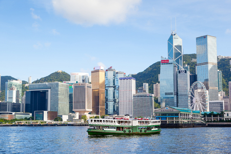 A ferry cruises Victoria harbour at Tsim Sha Tsui in Hong Kong, with the modern skyscrapers of the Central District looming in the background.