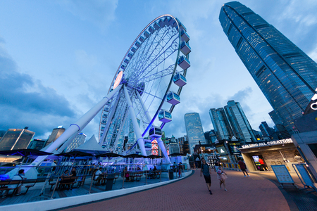 HONG KONG, JULY 10, 2017: Wide angle shot of the Observation Wheel at Hong Kongs Central Pier near Victoria Harbour during sunset with the downtown financial district in the background.