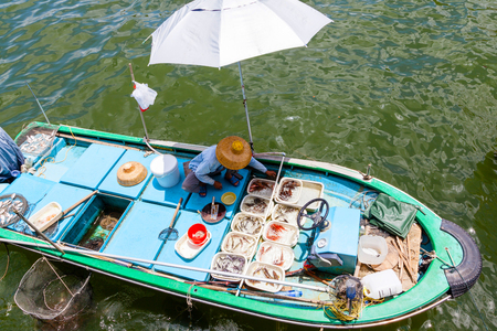 HONG KONG - JULY 13, 2017: A fisherman separates his live seafood catch into plastic containers on a boat at Sai Kungs floating seafood market. Every day, fishermen in boats alongside the Sai Kung harbor sell their fresh seafood to the public on the pier Editorial
