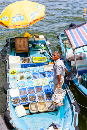 HONG KONG - JULY 13, 2017: A fisherman separates his live seafood catch into plastic containers on a boat at Sai Kungs floating seafood market. Fishermen in boats alongside the Sai Kung harbor sell their fresh seafood to the public on the pier. Editorial