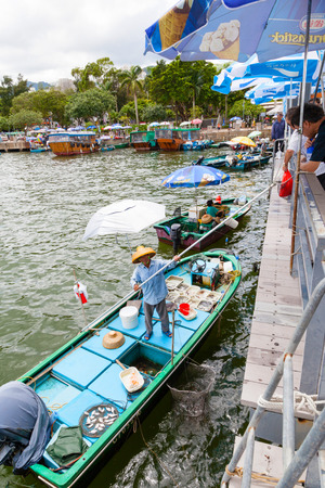HONG KONG - JULY 13, 2017: Fishermen in boats alongside the Sai Kung harbor sell their live seafood catch to the public on the pier with the aid of a long pole. Vertical orientation.