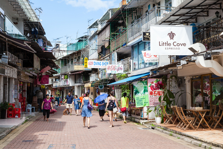 HONG KONG - JULY 14, 2014: Tourists and locals stroll along Sai Kungs old neighborhood on See Cheung Street. Sai Kung village is a laidback seaside town famous for its seafood restaurants and floating seafood market.
