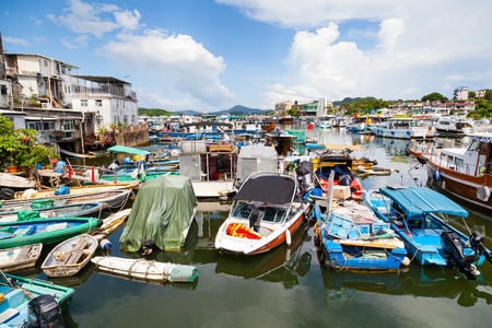 HONG KONG - JULY 13, 2017: Fishing and tour boats dock at the busy harbor in Sai Kung town famous for its quaint fishing villages and the floating seafood market. Sai Kung is also popular for its boat tours to nearby islands. Editorial