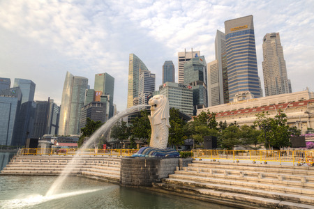 SINGAPORE - SEPTEMBER 11, 2017: Morning sunrise at Marina Bay with the iconic Merlion and the downtown central business district in the background. The Merlion is the citys most recognizable icon depicted as a mythical creature with a lions head and the Editorial