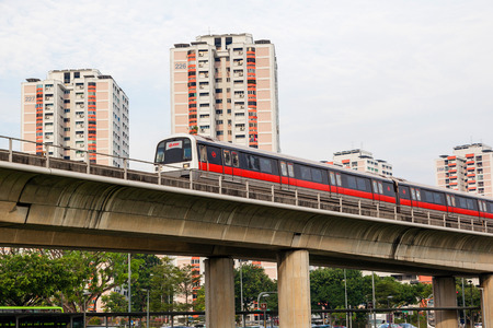 SINGAPORE - SEPTEMBER 11, 2017: Singapore's Mass Rapid Transit (SMRT) subway train travels on elevated rails through a public housing estate. The SMRT is the second-oldest metro system in Southeast Asia, after Manila Light Rail Transit System.